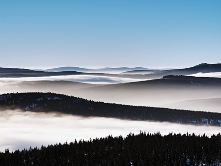 inversion: Chill weather inversion in winter mountains, heavy mist. Valley full of fog. Peaks of mountains above creamy mist.