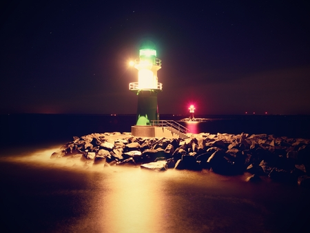 The ighthouse shinning at port gate. Modern light house at the end of stony pier in the dark night. Warnemunde on the Baltic Sea at the harbor entrance, Germany Stock Photo