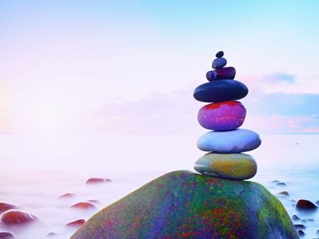 Gestapelde ronde stenen op zee. Kleine opgepoetste kiezelstenenstapel op donkere natte rots, blauw vlot water van oceaan op achtergrond Stockfoto