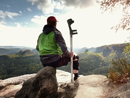 Tired tourist with medicine crutch  and broken leg fixed in immobilizer resting on  mountain summit. Valley bellow sitting man in green windcheater andd red baseball cap. Sharp sandstone edge. Stock Photo