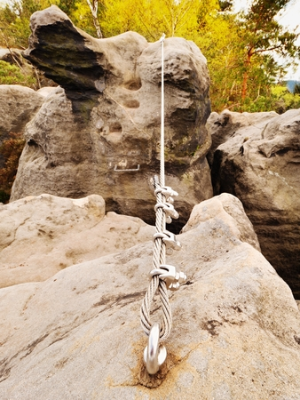 Iron twisted rope stretched between rocks in climbers patch via ferrata.  Rope fixed in block by screws snap hooks. Detail of rope end anchored into sandstone rock