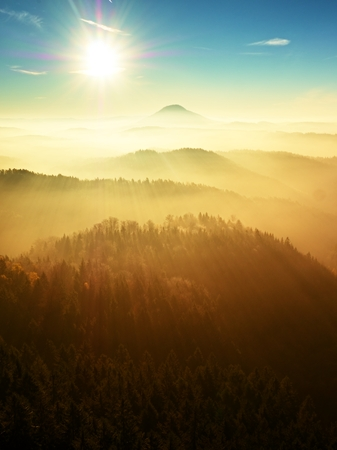 Red daybreak. Misty sunrise in the mountains, the gradation of color clouds. Misty daybreak in a beautiful hills. Peaks of hills are sticking out from foggy background, the fog is red and orange