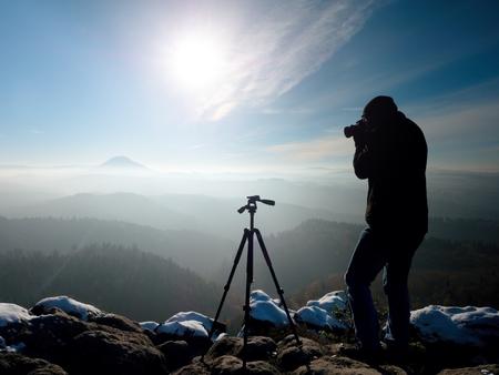 Fotograf takesfotografie zmrazit podzimní svítání, skály pokryté čerstvým prachem sněhu. Kamenný skalní vrchol vzrostl z mlhavého údolí.
