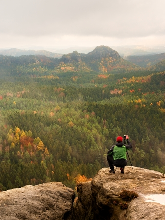 Hobby photographer takes a picture of a nature park from sharp rocks. Hiker in green jacket standing with camera on tripod on stony peak raised from foggy valley. Stock Photo