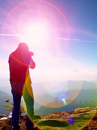 Tall  man is taking photo by mirror camera on neck. Snowy rocky peak of mountain. Professional photographer takes photos with mirror camera on peak of snowy rock.