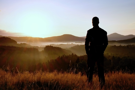 Tall hiker stand on meadow with golden stalks of grass and watch over misty and foggy morning valley to sunrise Stock Photo