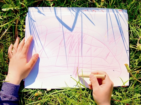 Close up view of childs hand drawing colorful ornaments on paper. Notebook in fresh grass of meadow.
