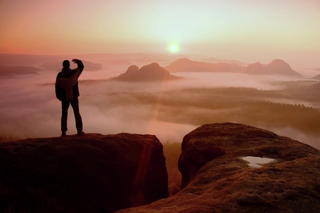 empires: Happy hiker is standing on the peak of  rock empires park and watching over the misty and foggy morning valley to Sun.