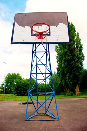 Old worn basketball hoopand  blue sky in background