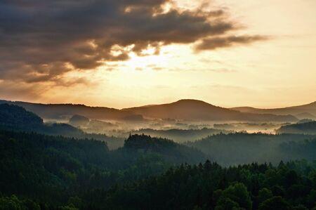 atractive: lighted rocks and hills bellow sunset sun on  horizon. Dark forest