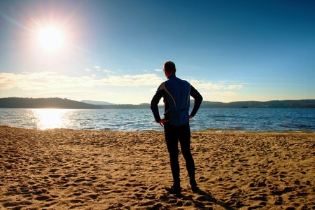 Silhouette of person in sportswear and short hair on beach seeing into morning Sun above sea Stock Photo