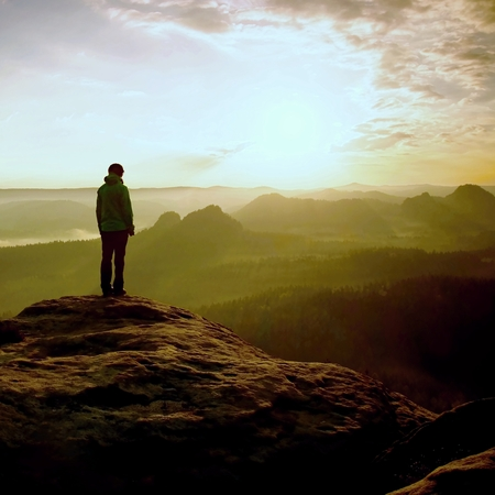 empires: Hiker stand on the sharp corner of sandstone rock in rock empires park and watching over the misty and foggy morning valley to Sun.