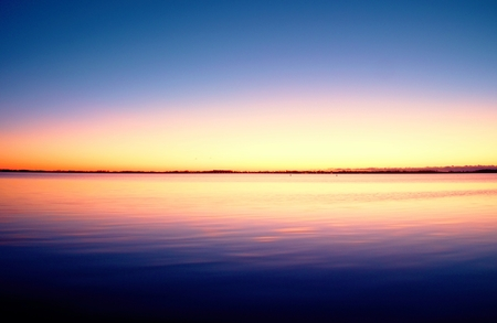 first day: The first light of day creates dramatic colors in the sky over the sea Stock Photo