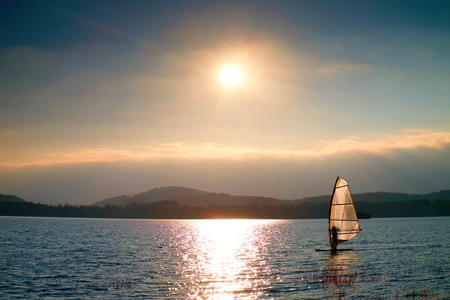 Windsurfer leans back into breeze Shot with gentle filter. Strong sun makes reflections in mirror of water level. Stock Photo