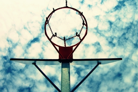 Old neglect basketball backboard with rusty hoop above street court. Blue cloudy sky in bckground.