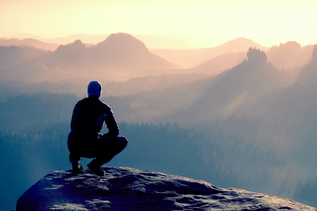 Young man in black sportswear is sitting on cliffs edge and looking to misty valley bellow