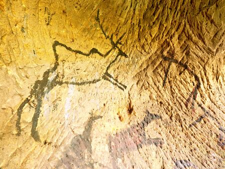 Black carbon paint of deer on sandstone wall, prehistorical picture. Abstract art in sandstone cave. Black carbon symbols on sandstone wall. Paint of human hunting,  prehistoric picture. Discovery of human history Stock Photo