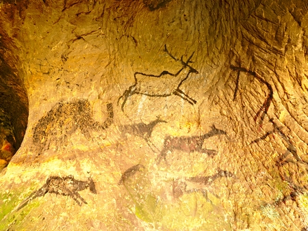 Discovery of prehistoric paint of caveman hunt in sandstone cave. Paint of human hunting of deers, mammoth and reindeer. Spotlight shines on historical black carbon abstract art in sandstone cave