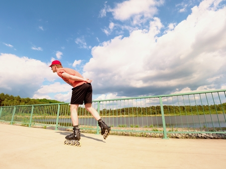 blading: Rear view to inline skater in red t-shirt and black pants skating on the bridge . Outdoor inline skating on smooth concrete ground on lake bridge. Light skin man in four wheel boots