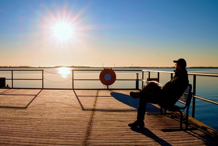 Man sit on bench on wharf construction and looking at sea. Sunny clear blue sky, smooth water level