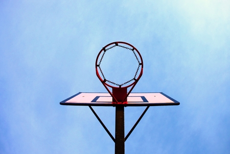 Old neglect basketball backboard with rusty hoop above street court. Blue sky in background.