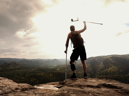 Happy man hiking holding medicine crutch above head, injured knee fixed in knee brace feature. Scenic mountain top with deep cloudy valley below Stock Photo