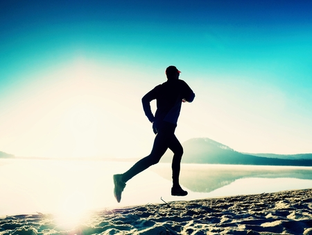 Healthy lifestyle. Tall young man runner is running on sunrise seaside. Man jump in wet sand of the bay beach Stock Photo