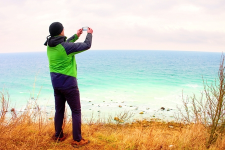 Man in green waterproof jacket takes photo of coastliny by smart phone. Cold windy day on reef above  sea. Stock Photo