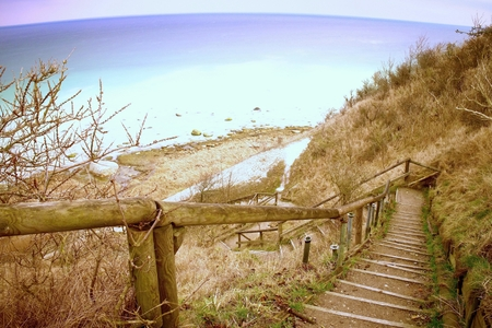 Old wooden stair way down with wooden hadrail, steps  down to  sea shore hill. Vintage effect Stock Photo