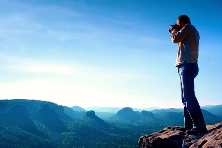 Professional photographer takes photos with big camera on peak of rock. Dreamy misty landscape, hot Sun above Stock Photo