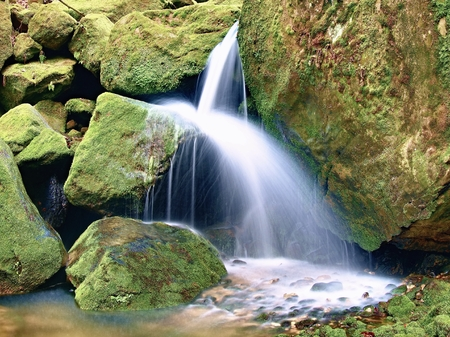 Weir in mountain stream. Colorful leaves  on stones into water. Mossy boulders.