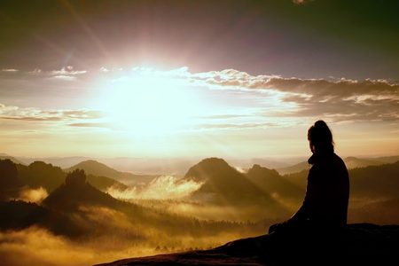 Beautiful  young woman tourist enjoy daybreak on the sharp corner of sandstone rock and watch over valley to Sun.