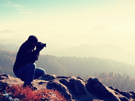 humid: Photographer down on knees takes photos with mirror camera on peak of rock. Dreamy landscape, orange Sun at horizon