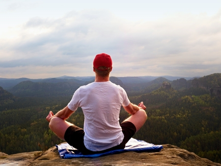 foggy hill: Alone sitting man practicing Yoga pose on the rocky peak.  Man within misty morning do meditation and  enjoying valley view Stock Photo