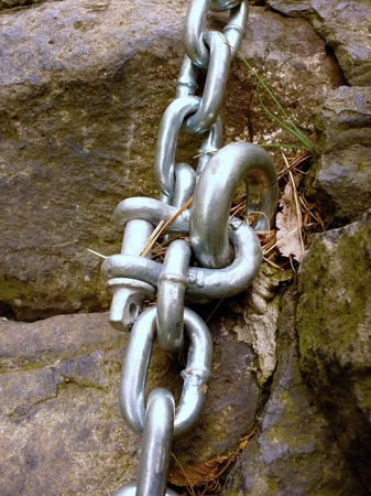 Detail of chain and steel bolt anchor eye in sandstone rock. The end knot of steel chain. Climbers path via ferrata. Iron chain fixed in block. Stock Photo