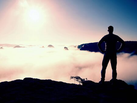 a wonderful world: Man in shirt and jeans is standing on the peak of sandstone empire  and watching over the misty and foggy morning valley to Sun. Beautiful moment the miracle of nature Stock Photo