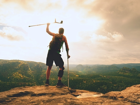 Man with a crutches and a broken leg fixed in a knee brace feature.Traveler with a hurt leg in bandages stay on a rocky view point in the mountains. Hiker with broken leg in immobilizer. Standard-Bild