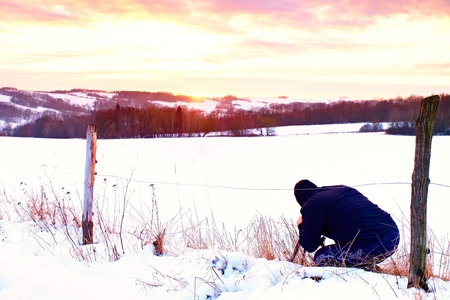 frosty morning: Photographer lay in snow on meadow and takes a picture of fantastic sunset above opposite hill