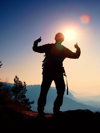 Happy man gesture of triumph. Funny hiker on the peak of sandstone rock in national park Saxony Switzerland watching into camera, the Sun behind head. Stock Photo
