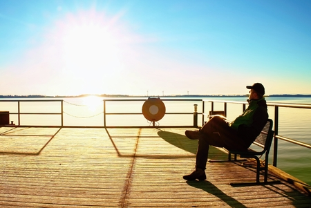 Tourist sit on wharf construction and enjoy morning at sea. Sunny clear blue sky, smooth water level Stock Photo