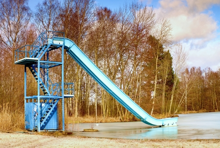 Old blue sliding track on lake beach, frozen watel level. Winter time at natural swimming resort