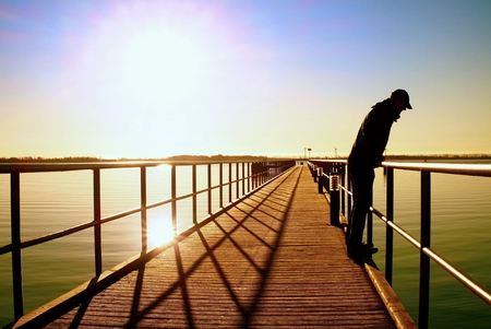 Alone man on pier and look over handrail into water. Sunny clear blue sky, smooth water level