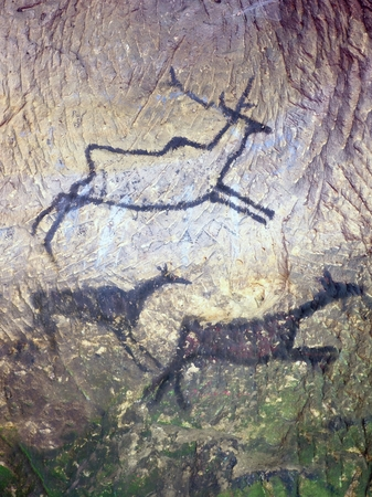 Black carbon paint of deer on sandstone wall, copy of prehistoric picture. Abstract children art in sandstone cave. 版權商用圖片