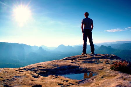 strip shirt: Alone hiker in red cap stand on the peak of sandstone rock in rock empires park and watching over the misty and foggy morning valley to Sun. Beautiful moment the miracle of nature Stock Photo