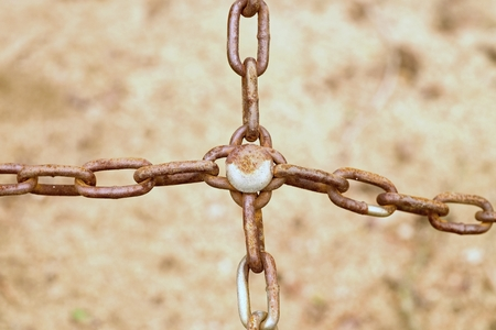 Joined old rusty chain in cross, close up view of poor chain and screw