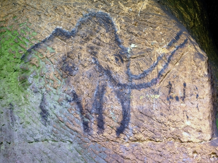 Abstract children art in sandstone cave. Black carbon mammoth paint of human hunting on sandstone wall, copy of prehistoric picture.