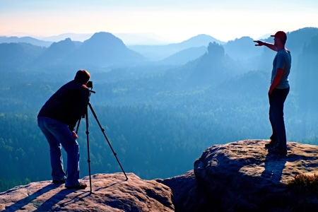 Hiker and photo enthusiast stay with tripod on cliff and thinking. Dreamy fogy landscape, blue misty sunrise in a beautiful valley below Stock Photo