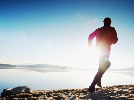 活発な男性運動と日の出湖ビーチでストレッチのシルエット。健康的なライフ スタイル。朝ビーチで単独で若いフィットネス男をエクササイズしま