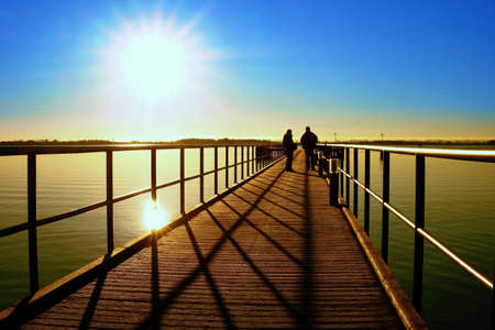 Morning in harbor. Tourists walk on pier construction above sea. Sunny clear blue sky, smooth water level