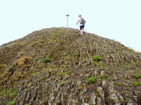 Hiker climbing on sharp peak of basalt formation. Long basalt poles of cold volcano.  Stock Photo